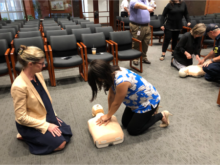 Two people doing CPR on practice dummy