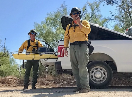 Two men holding rescue equipment: a walkie talkie and an emergency stabilizer transport bed