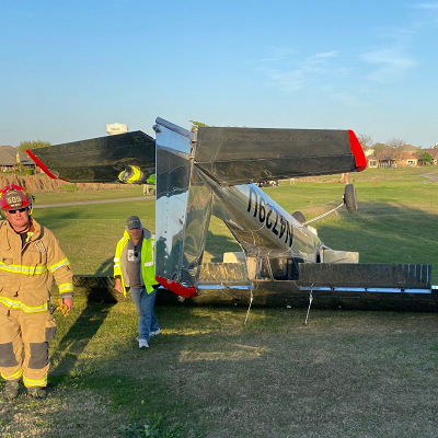Small airplane upside down on grass with firefighters standing nearby